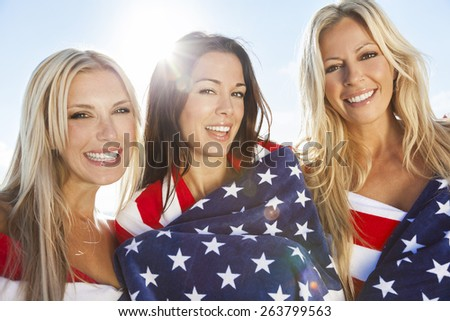 Three beautiful young women wearing bikinis, wrapped in American flags, smiling, laughing and having fun party on a sunny beach - stock photo