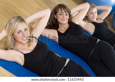Three beautiful young women working out at the gym, the focus is on the brunette girl in the center - stock photo
