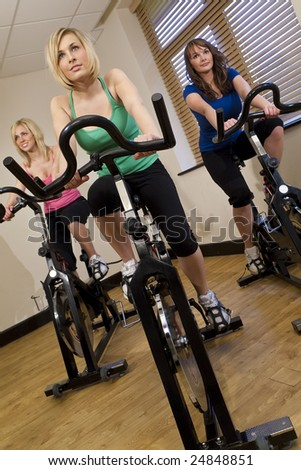 Three beautiful young women working out on  bikes at the gym - stock photo
