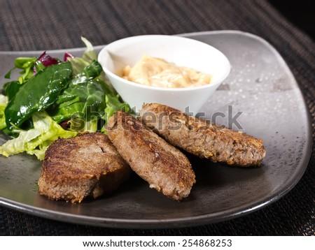 three beef Patties with Yogurt, Sour Cream and salad on black background  - stock photo