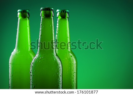 Three beer bottles against vivid green background - stock photo