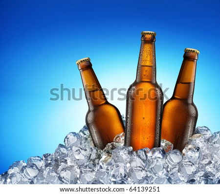 Three beer bottles getting cool in ice cubes. Isolated on a blue. File contains a path to cut - stock photo