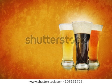 Three beer glasses have foam and are on a golden background with a rough texture. Use it for a Bar or celebration concept. - stock photo