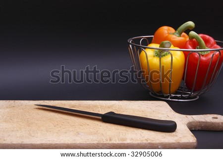 three bell peppers in chrome basket and chopping board - stock photo