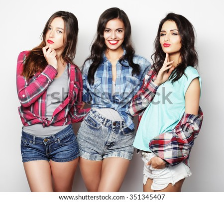 Three best friends posing in studio, wearing summer style outfit and jeans shorts. Girls smiling and having fun. - stock photo