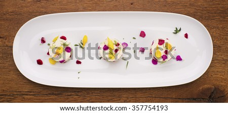Three bite-size mini cheesecakes on a white porcelain plate decorated with colorful flower petals. Gourmet food. - stock photo