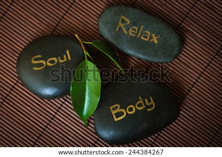 Three black massage stone with words Body, Soul and Relax - stock photo