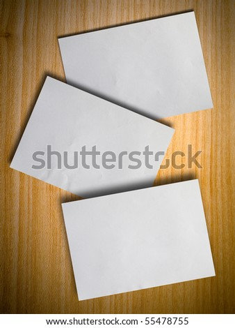 Three blank paper on wood wall with shadow - stock photo