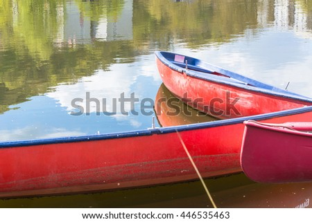 Three blank red canoes lie in the river secured to a jetty on the shore. - stock photo