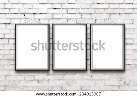 Three blank vertical painting poster in black frame hanging on white brick wall. Painting proportions match international paper size A. - stock photo