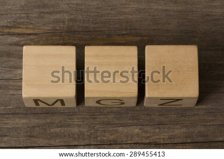 three blank wooden blocks on a wooden background with copyspace for your text, letters or numbers - stock photo