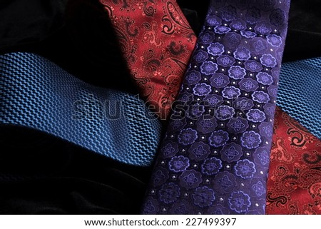 Three (blue, purple and red) silk ties crossing on top of the other, while on display on black velvet - stock photo