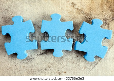 Three blue puzzle pieces on old canvas background - stock photo