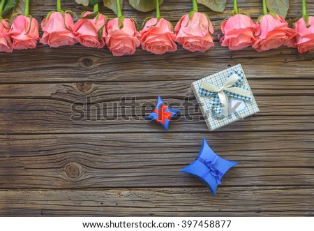 Three blue, red and white various Valentines Day bowed gift boxes over worn out wooden background with roses on top - stock photo