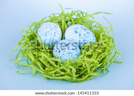 Three blue speckled easter eggs in green paper grass nest - stock photo