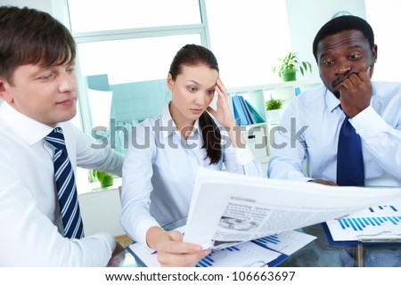 Three bored colleagues reading newspaper at meeting - stock photo
