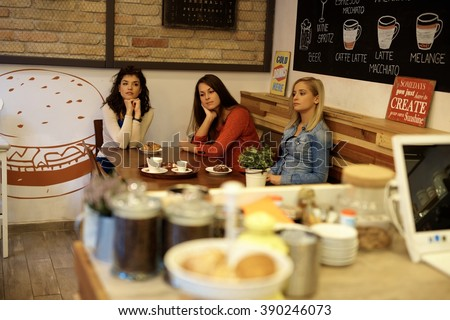 Three bored young single girls sitting in cafeteria, having coffee and cakes. - stock photo