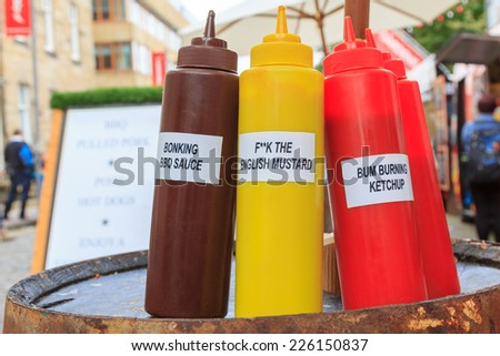 Three bottles for BBQ sauce, mustard, and ketchup with funny labels on a market - stock photo