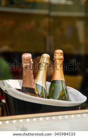 three bottles of champagne in an ice bucket - stock photo