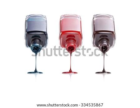 three bottles of nail polish flow on white background - stock photo