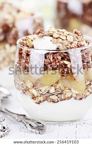 Three bowls of red quinoa with apples, yogurt and granola with shallow depth of field. - stock photo