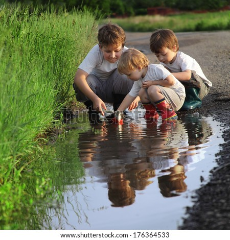three boy play in  puddle - stock photo