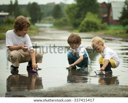 three boy play in puddle summer day - stock photo