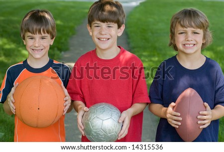 Three Boys Holding Sports Balls - stock photo