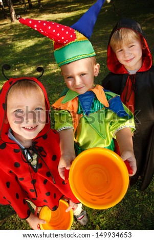 Three boys in halloween costumes trick or treating.  Shooted with wide-angle lens effect - stock photo