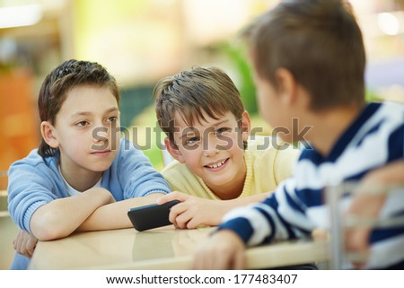 Three boys talking indoors - stock photo