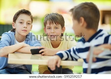 Three boys talking indoors - stock photo