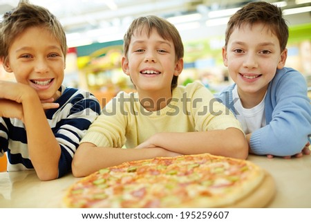 Three boys thrilled with pizza looking at camera - stock photo