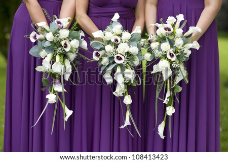 three bridesmaids in purple dresses holding wedding bouquets - stock photo