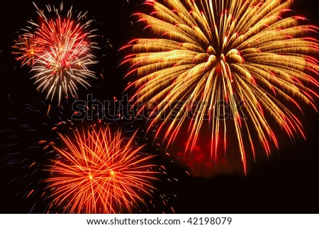 Three bright bursts of fireworks, with gold predominating - stock photo