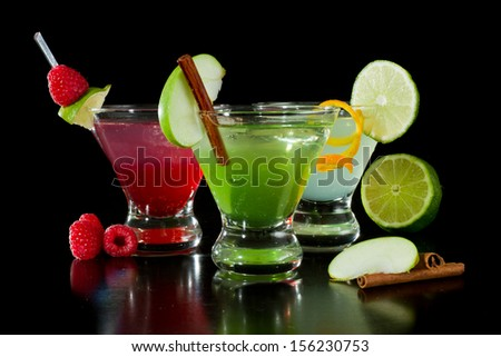 three bright martinis garnished with fresh fruit isolated on a black background - stock photo