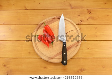 Three bright red baby peppers with a sharp kitchen knife on a wooden chopping board  - stock photo