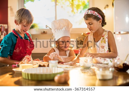 Three brother and sisters are smiling, cooking together in a luminous kitchen. They are standing close to each other at a wooden table, working on a spread pastry in order to make small cakes. - stock photo