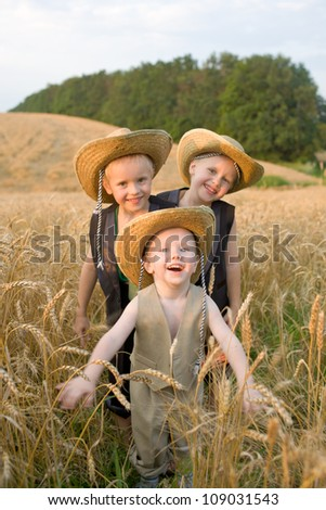 Three brothers funny playing field of wheat. The two older boys - twins. Smiling big family. Happy family concept. Summer holiday. - stock photo