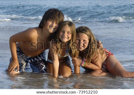 Three brothers posing in the beach - stock photo