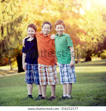Three brothers standing outside with Instgram style filter - stock photo