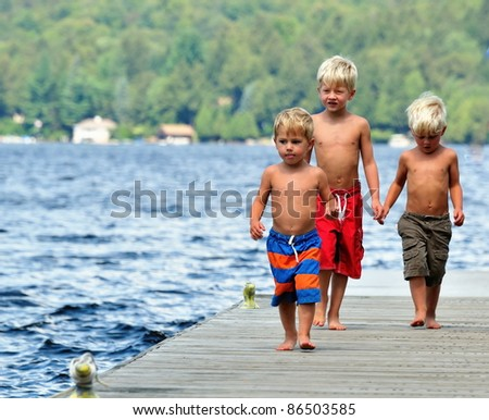 Three brothers walk along the dock on a sunny day - stock photo