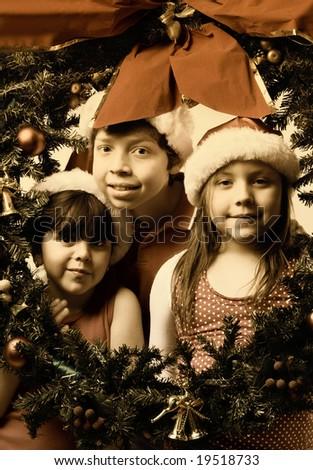 three brothers wearing santa hats inside a green christmas wreath - stock photo