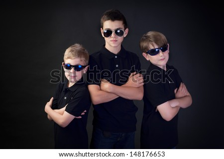 Three brothers with attitude dressed as FBI detectives - stock photo