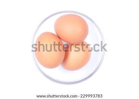 Three brown eggs in a glass bowl isolated on white background top view - stock photo