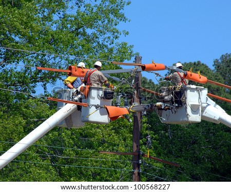 Three buckets trucks lift linemen to top of electricity pole. Three repairmen combine knowledge and repair power outage. - stock photo