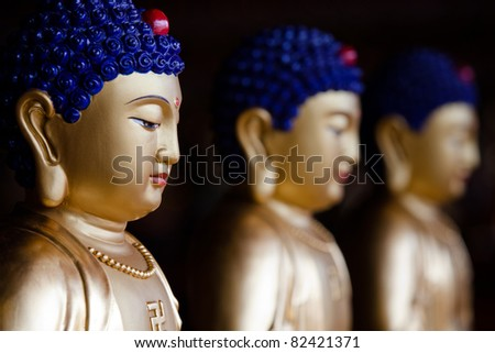 Three Buddha Statue with moderate depth of field and focus on front buddha - stock photo