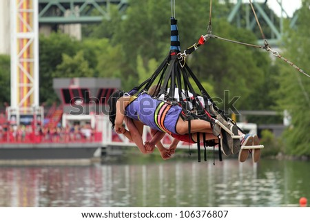 three bungee jumpers with security equipment - stock photo