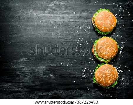 Three burgers with meat, cheese and fresh vegetables. On a black chalkboard. Top view. - stock photo