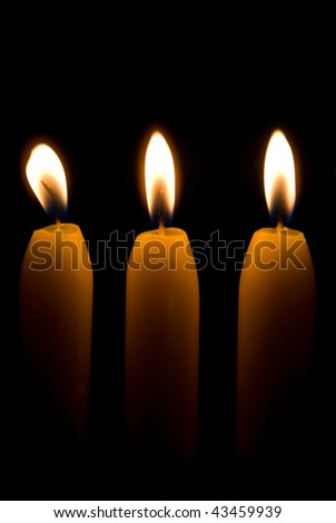 Three burning candles over a black background - stock photo