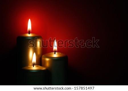 Three burning gold candles - stock photo